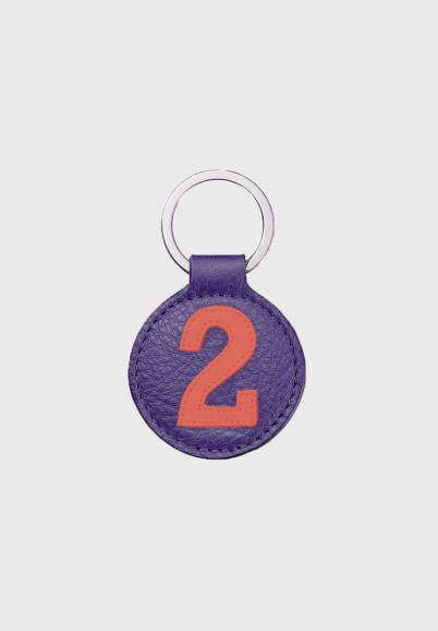 Round leather key ring with coral number and purple background